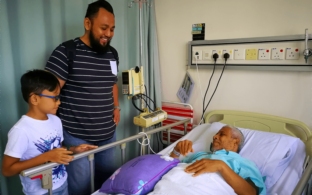 man and son with older man at hospital