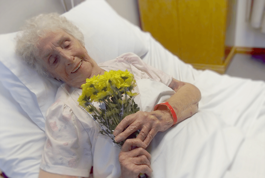 woman in hospital bed holding flowers