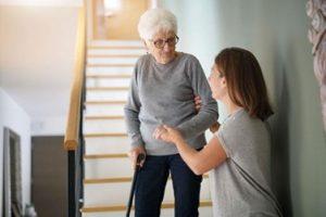 women helping elderly woman down the stairs